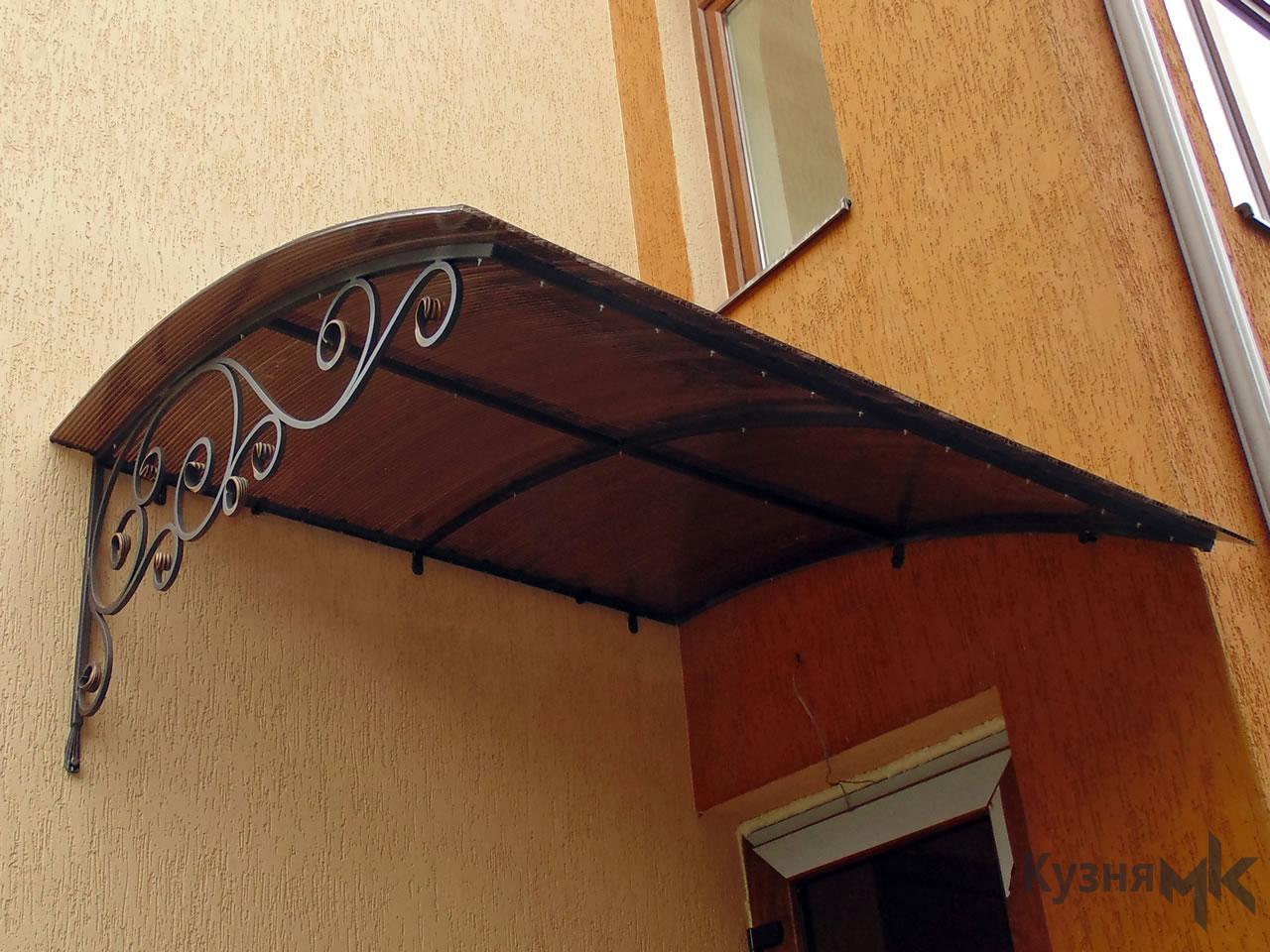 Кований дашок над входом в будинок